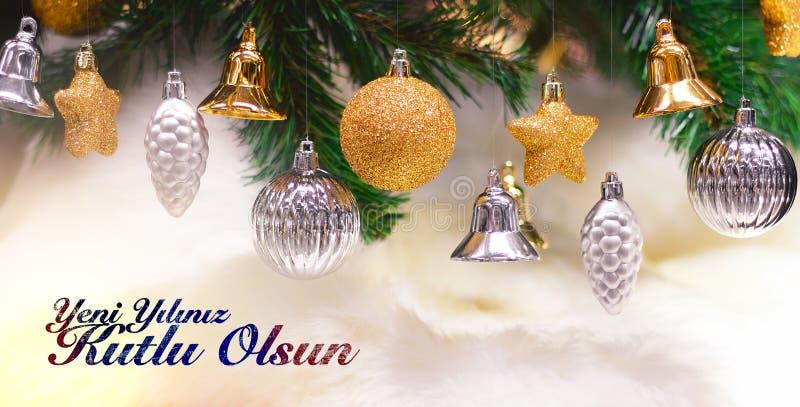 Glänzendes Gold und silberne Weihnachtsbälle, Sterne und Glocken auf Weiß mit Kiefer Yeni-yiliniz kutlu olsun Durchschnittguten r stockbild