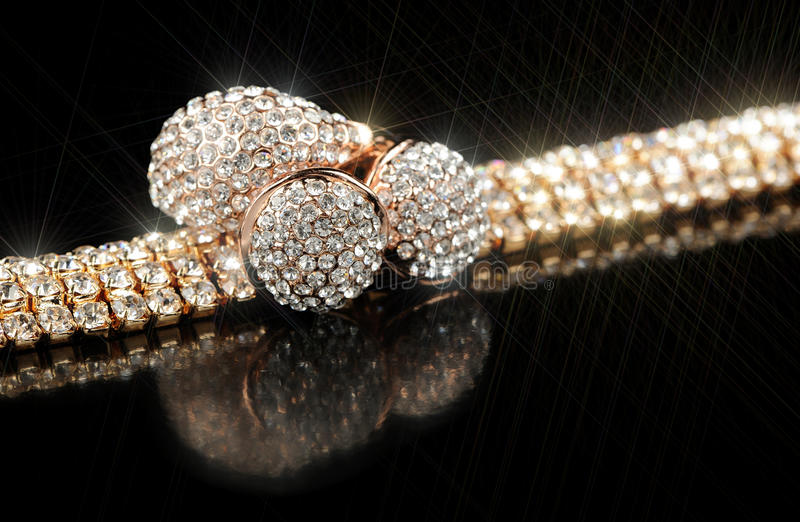 Glänzendes Goldarmband, -ohrringe und -ring auf schwarzem Hintergrund lizenzfreie stockbilder