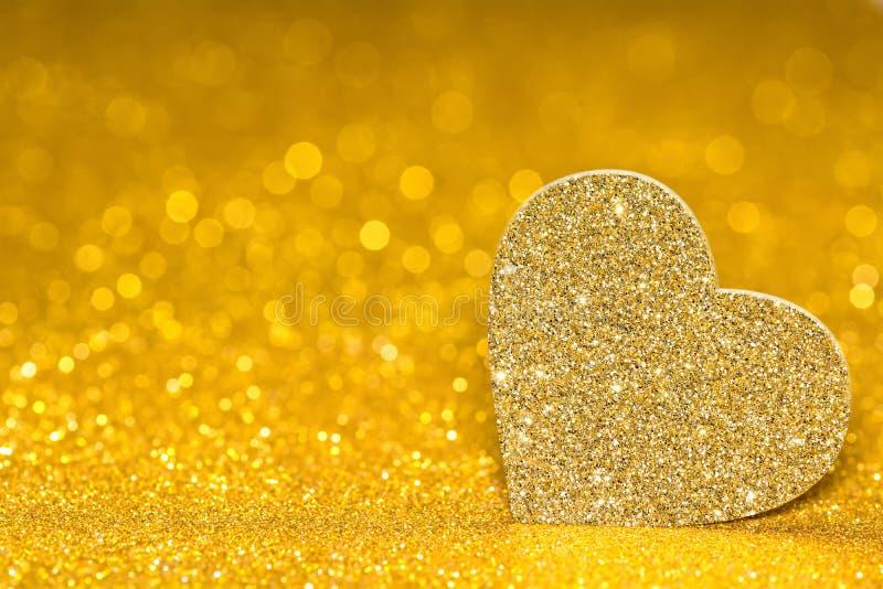 Glänzendes Herz auf einem goldenen leuchtenden Hintergrund Funkelnglanz mit Form 3d stockfotografie