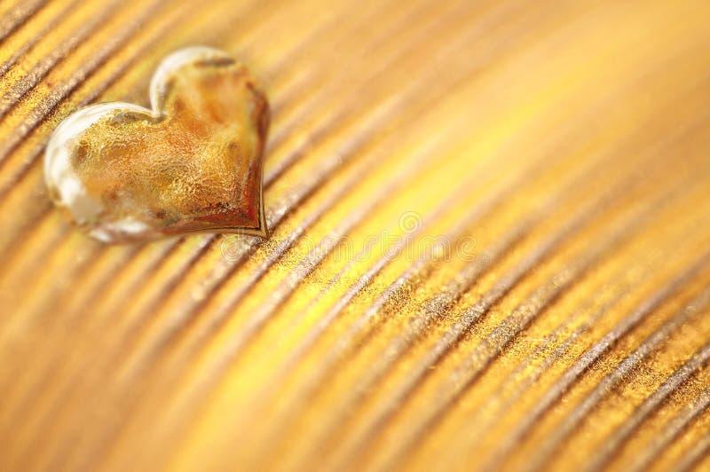 Glänzendes kleines goldenes Herz auf Goldpulver stockbild
