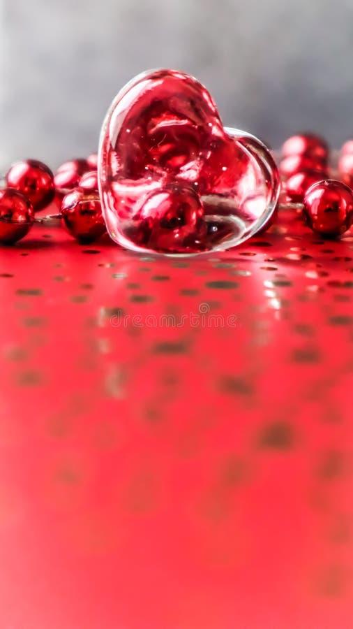 Glänzendes transparentes Herz und eine Gruppe rote Perlen Perfekter Valentinsgruß-Tagesgrußkartenhintergrund Vertikales Bild im r lizenzfreies stockfoto