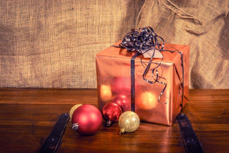 Glänzendes Weihnachtsgeschenk auf einem Holztisch stockfotos