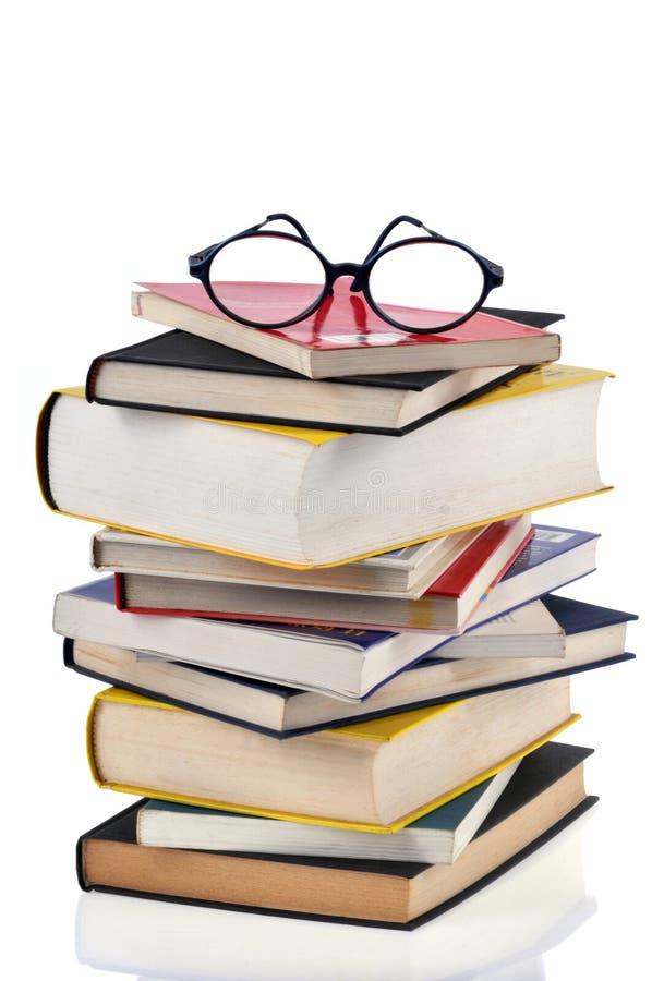 Gläser auf einem Stapel der Bücher stockbilder