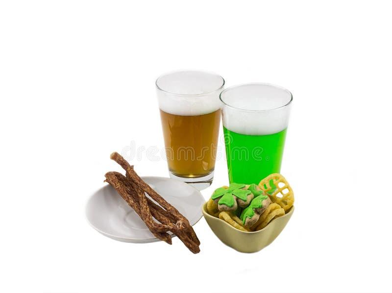 Gläser Bier grünen Lager mit Klee mit köstlicher Wurst auf einem Snack auf einem weißen Hintergrund Fest von St- Patrick` s Tag lizenzfreie stockbilder