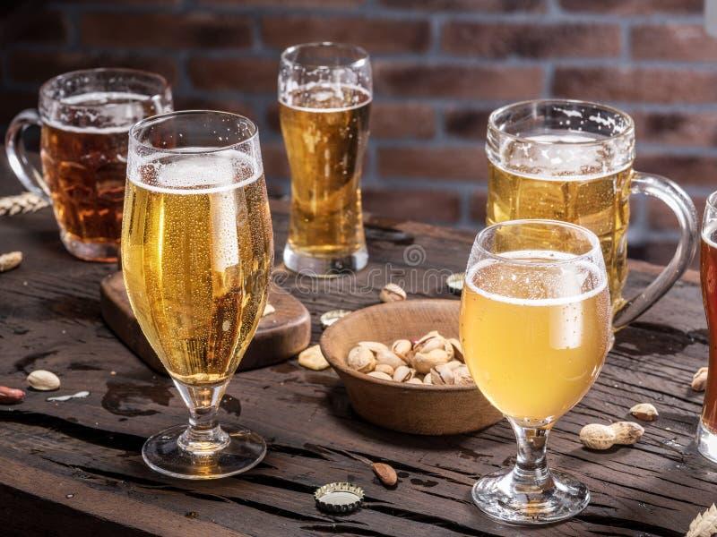 Gläser Bier und Snäcke auf dem Holztisch lizenzfreies stockbild