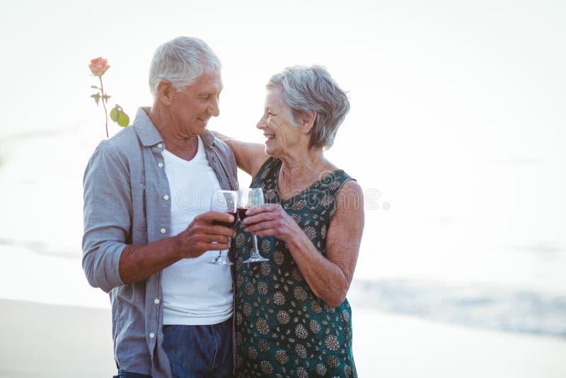 Gläser des rosafarbenen und Rotweins der älteren Paarholding lizenzfreies stockfoto