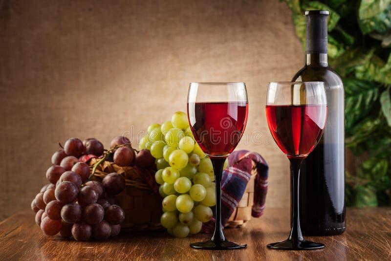 Gläser des Rotweins und der Flasche stockfotografie