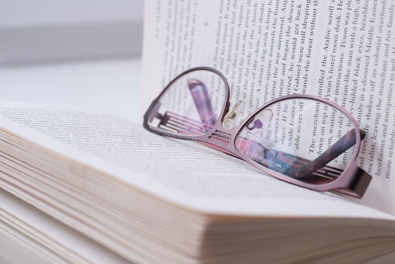 Gläser, die auf einem Buch liegen stockfotos