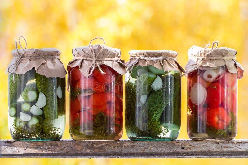 Gläser in Essig eingelegtes Gemüse: Gurken, Tomaten auf einem hölzernen shel stockbild