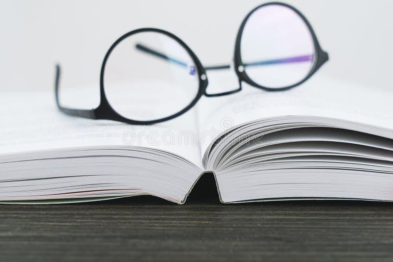 Gläser für das Ablesen auf einem offenen Buch stockfotos
