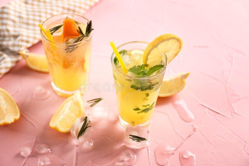 Gläser kalte geschmackvolle Cocktails auf Farbstrukturierter Tabelle stockbild