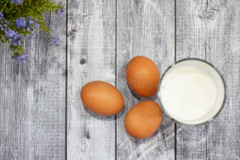 3 Gl?ser Milch und Eier, auf einem grauen h?lzernen Hintergrund, Nahrunggetr?nkehintergrund stockbilder