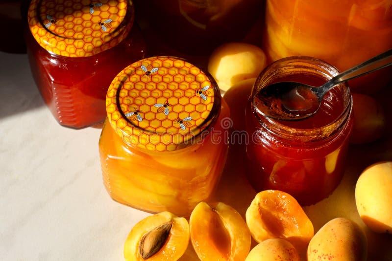 Gläser mit Aprikosen- und Pflaumenstau auf einem hölzernen Hintergrund lizenzfreie stockfotografie