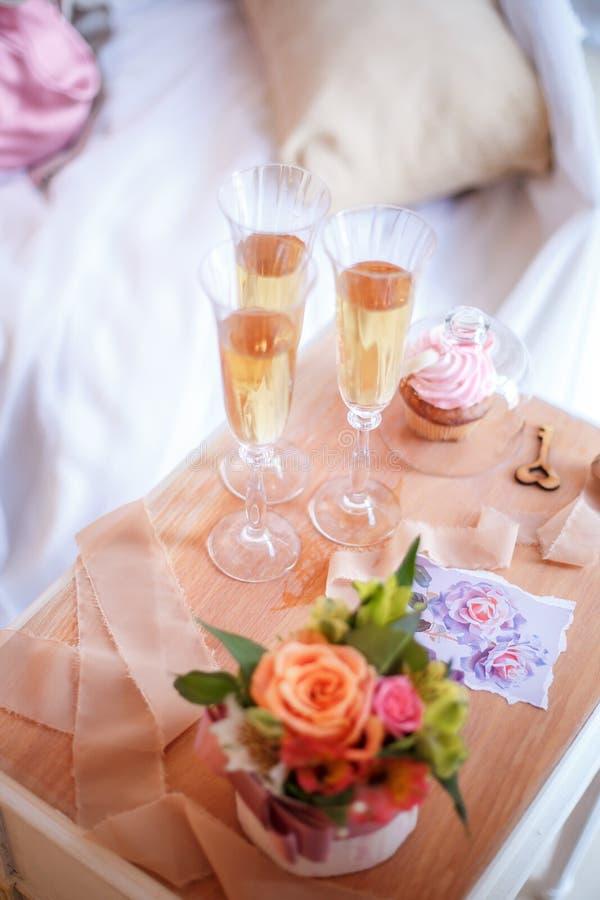 Gläser mit Champagner, Kuchen, Blumen, hölzernem Schlüssel und Bändern auf dem Nachttisch stockfotografie