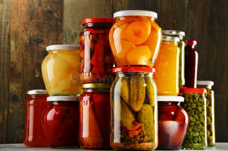Gläser mit in Essig eingelegtem Gemüse, fruchtigen Kompotten und Staus lizenzfreie stockfotos