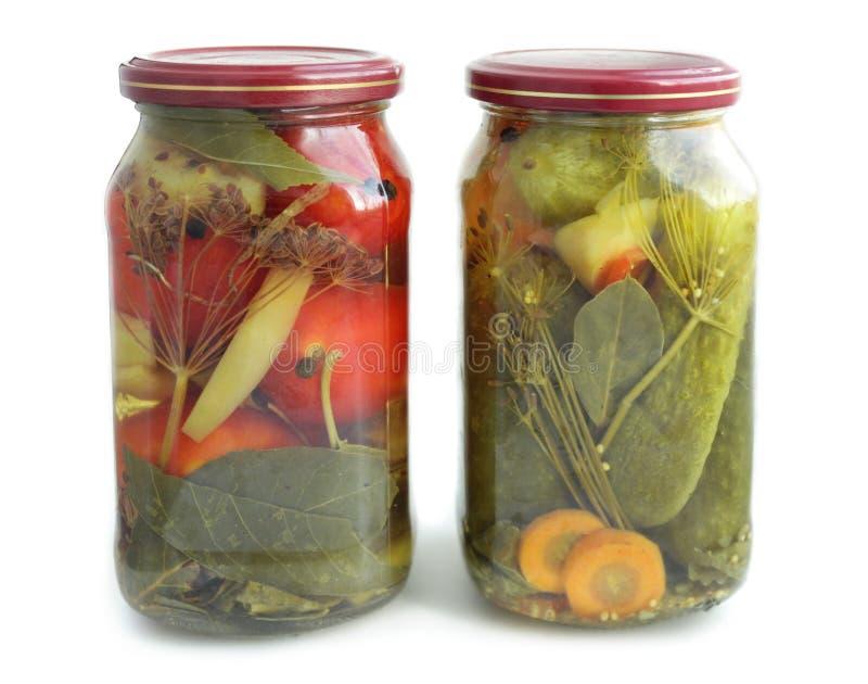 Gläser mit in Essig eingelegten Gurken und den Tomaten lokalisiert auf Weiß lizenzfreie stockfotos