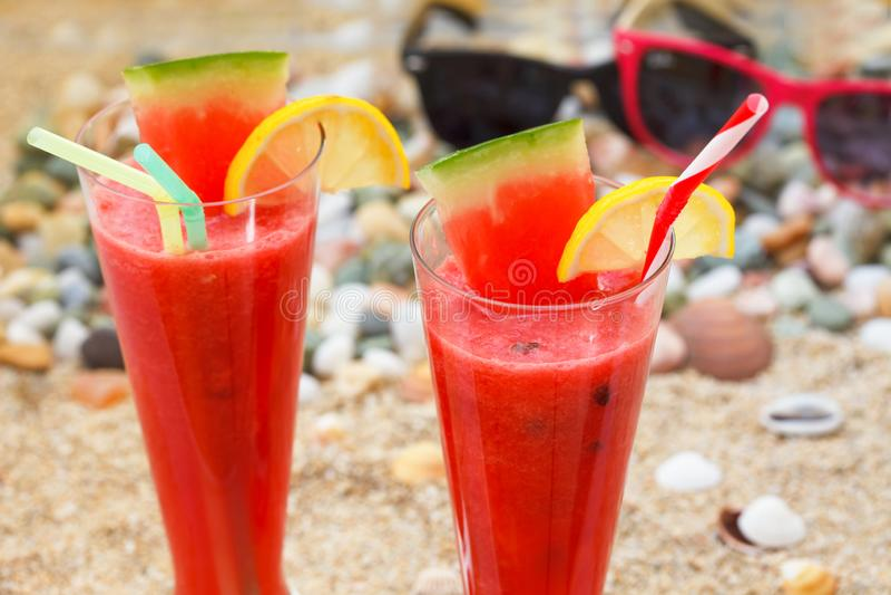 Gläser mit frischen Wassermelonensäften auf sandigem Strand stockfotos