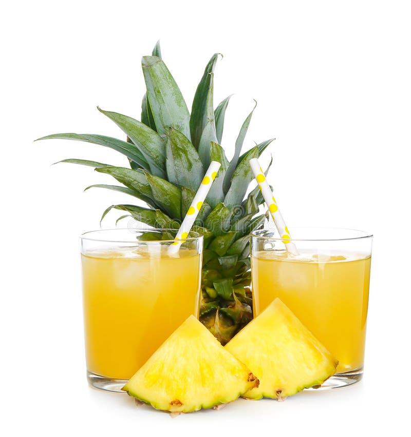 Gläser mit geschmackvollem frischem Ananassaft und ganzer Frucht auf weißem Hintergrund lizenzfreies stockfoto