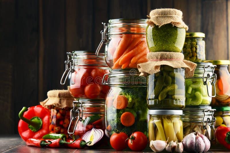 Gläser mit mariniertem Lebensmittel und organischem rohem Gemüse stockfotografie