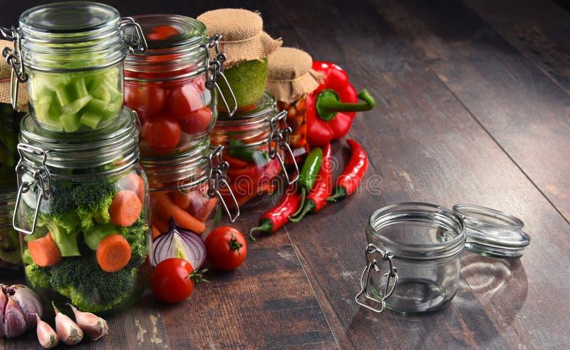 Gläser mit mariniertem Lebensmittel und organischem rohem Gemüse lizenzfreie stockfotografie