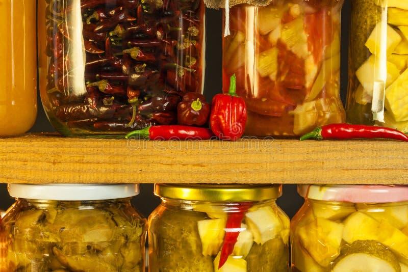 Gläser mit mariniertem Lebensmittel und organischem rohem Gemüse Konserviertes Gemüse auf hölzernem Hintergrund Verschiedenes mar lizenzfreies stockbild