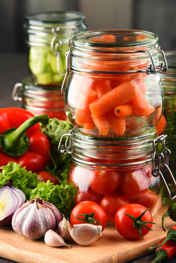 Gläser mit mariniertem Lebensmittel und rohem Gemüse auf Schneidebrett lizenzfreies stockfoto