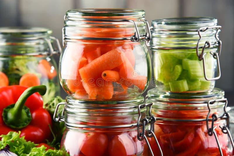 Gläser mit mariniertem Lebensmittel und rohem Gemüse auf Schneidebrett stockfoto