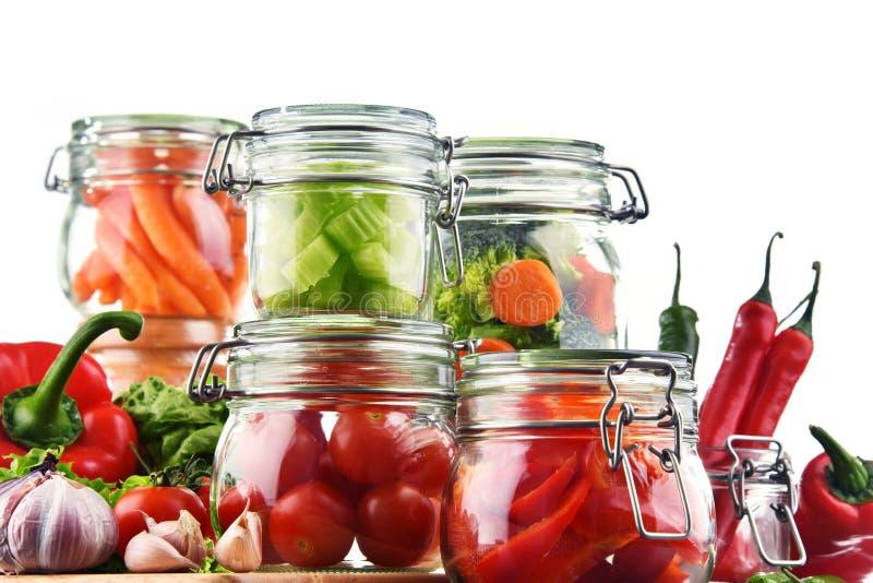 Gläser mit mariniertem Lebensmittel und rohen dem Gemüse lokalisiert auf Weiß lizenzfreie stockbilder