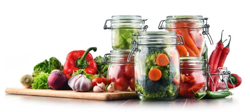 Gläser mit mariniertem Lebensmittel und rohen dem Gemüse lokalisiert auf Weiß stockfotografie