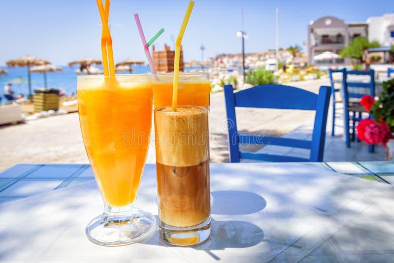Gläser mit Orangensaft und griechischem Kaffee frappe lizenzfreie stockfotos