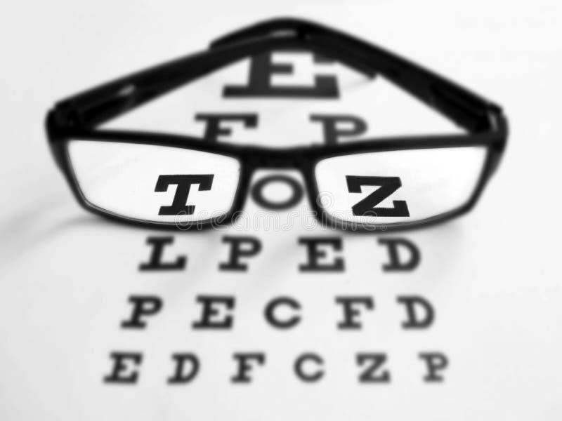 Gläser mit schwarzem Rahmen- und Sehtestdiagramm stockbilder
