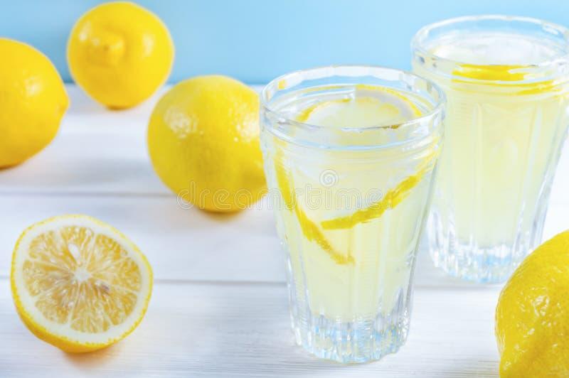 Gläser mit Sommergetränklimonade und Zitronenfrucht auf weißem Holztisch lizenzfreies stockfoto