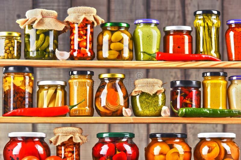 Gläser mit Vielzahl des in Essig eingelegten Gemüses stockfotografie