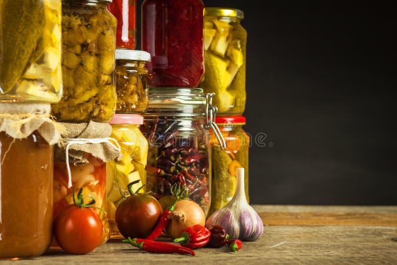 Gläser mit Vielzahl des in Essig eingelegten Gemüses Karotten, Feldknoblauch, Petersilie in den glas Konservierte Nahrung Ferment lizenzfreie stockfotos