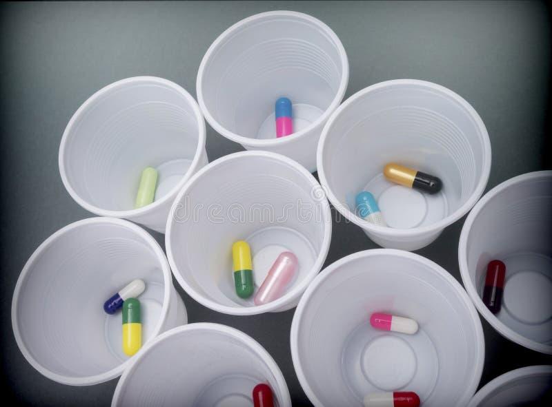 Gläser Plastikweiß mit täglicher Dosis der Medikation lizenzfreie stockfotos