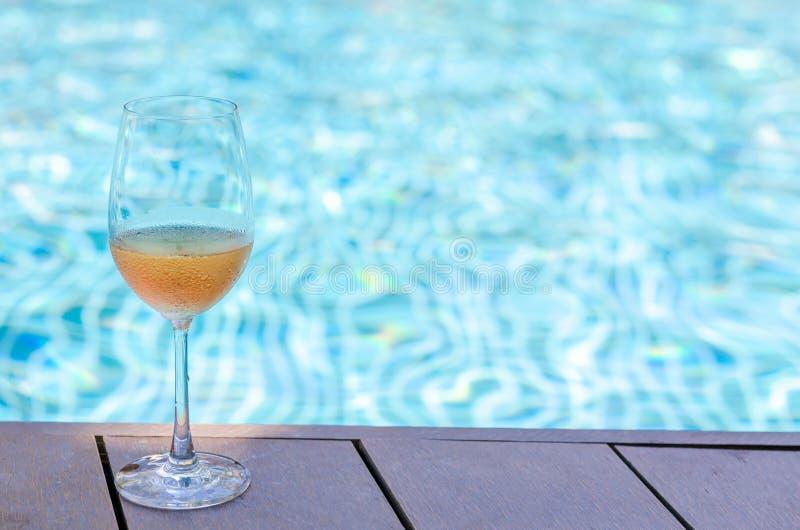 Gläser Rosen-Wein gesetzt auf Swimmingpool lizenzfreies stockfoto