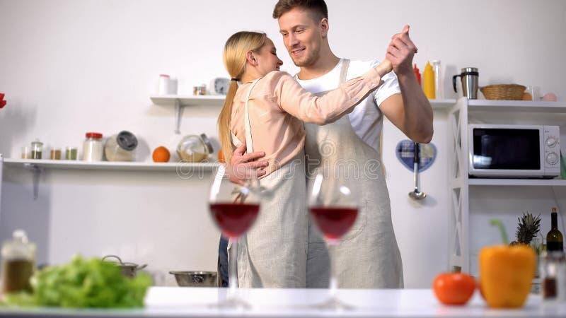 Gläser Rotwein auf Tabelle, romantisches Paartanzen auf Hintergrund in der Küche stockfoto