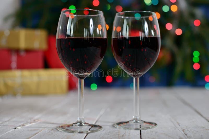Gläser Rotwein mit Weihnachtsdekoration stockfotos