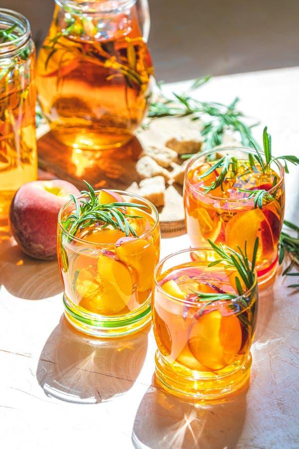 Gläser süßes Pfirsicheistee, kalter Pfirsich des Sommers sprudeln Cocktail mit Rosmarin Sonnige Leuchte Flache Tiefe des Feldes,  lizenzfreies stockbild