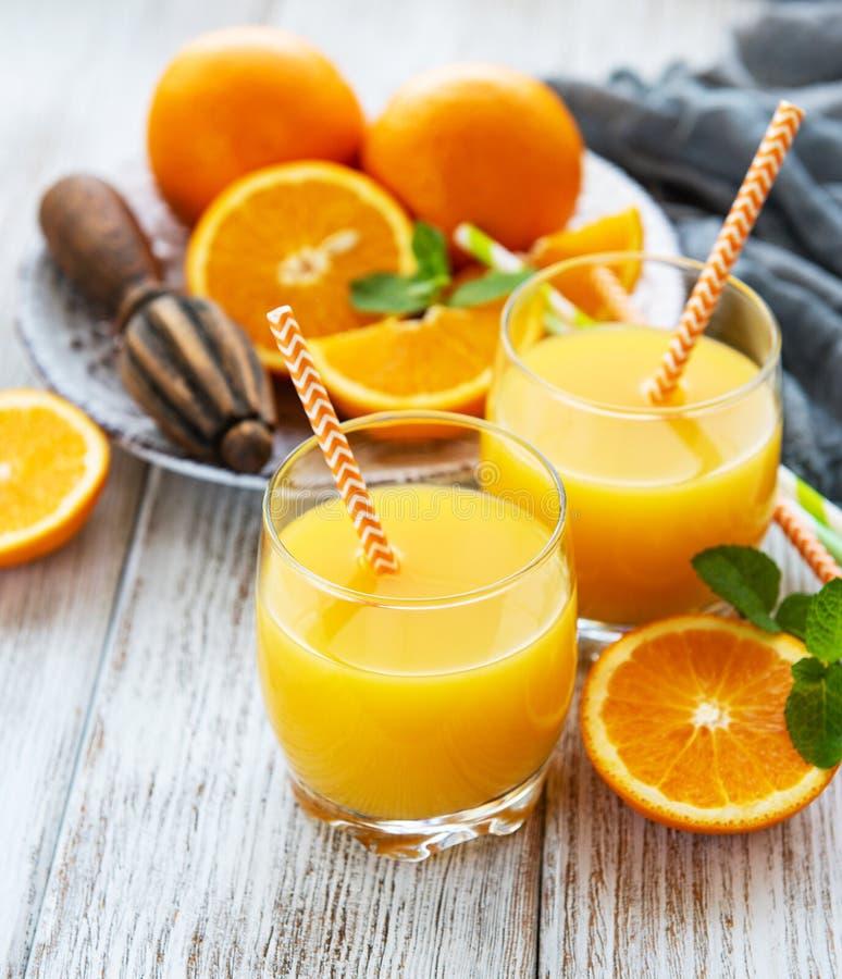 Gläser Saft und orange Früchte stockfotografie