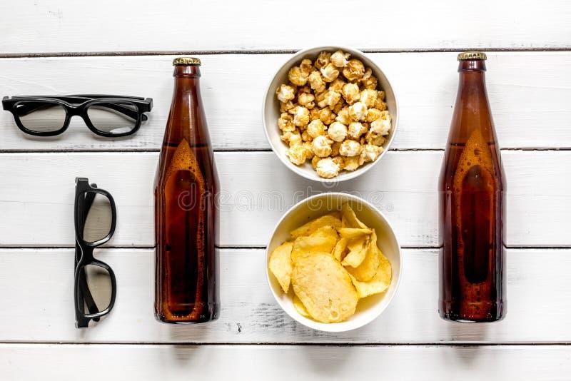 Gläser, Snäcke, Bier für whatchig Film auf Draufsicht des weißen hölzernen Hintergrundes stockfotos