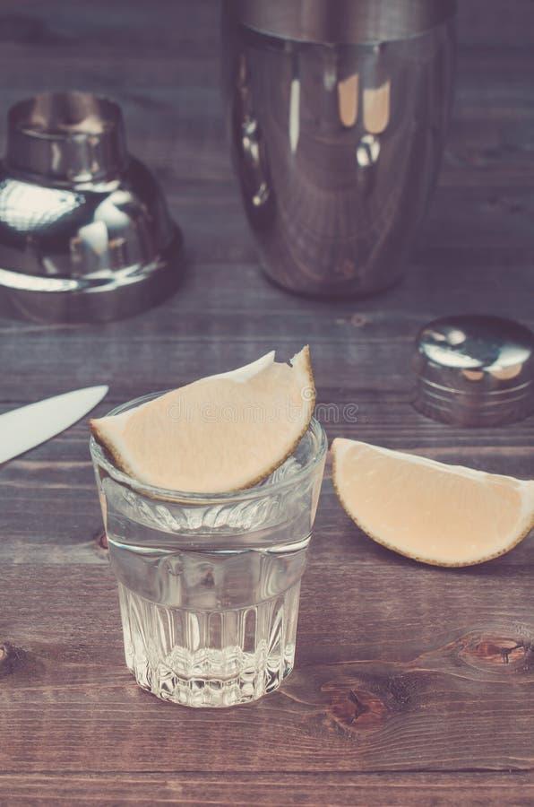Gläser Tequila mit einem Kalk/einer Vorbereitung des Schusses mit einem Kalk in einem Schüttel-Apparat auf einem hölzernen Hinter lizenzfreie stockfotos