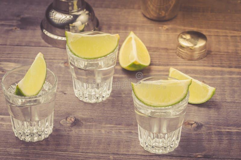 Gläser Tequila mit einem Kalk/einer Vorbereitung von Schüssen mit einem Kalk auf einem hölzernen Hintergrund stockfoto