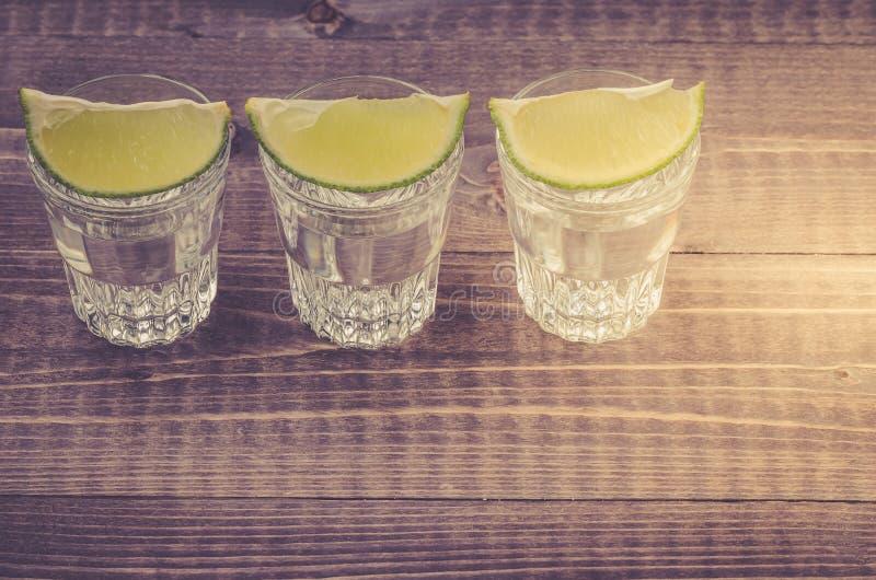 Gläser Tequila mit einem Kalk/Gläsern Tequila mit einem Kalkstand in Folge Kopieren Sie Platz Beschneidungspfad eingeschlossen stockfotografie