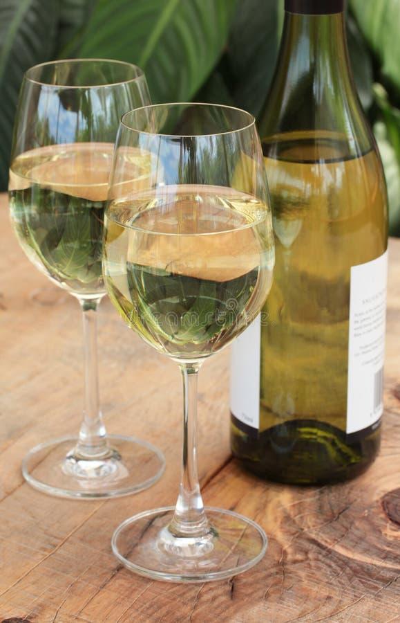 Gläser u. Flasche weißer Wein auf im Freientabelle stockbilder