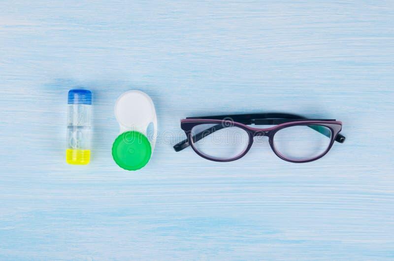 Gläser und Gegenstände für das Säubern und die Speicherung von Kontaktlinsen, um Vision, auf einem blauen Hintergrund zu verbesse lizenzfreie stockfotos