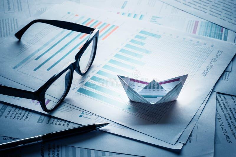 Gläser und Stift mit den Booten hergestellt vom Papierdiagramm stockbilder