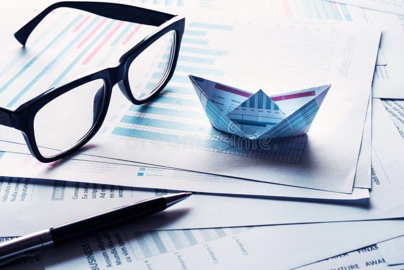 Gläser und Stift mit den Booten hergestellt vom Papierdiagramm auf Geschäftsdokument lizenzfreie stockfotos
