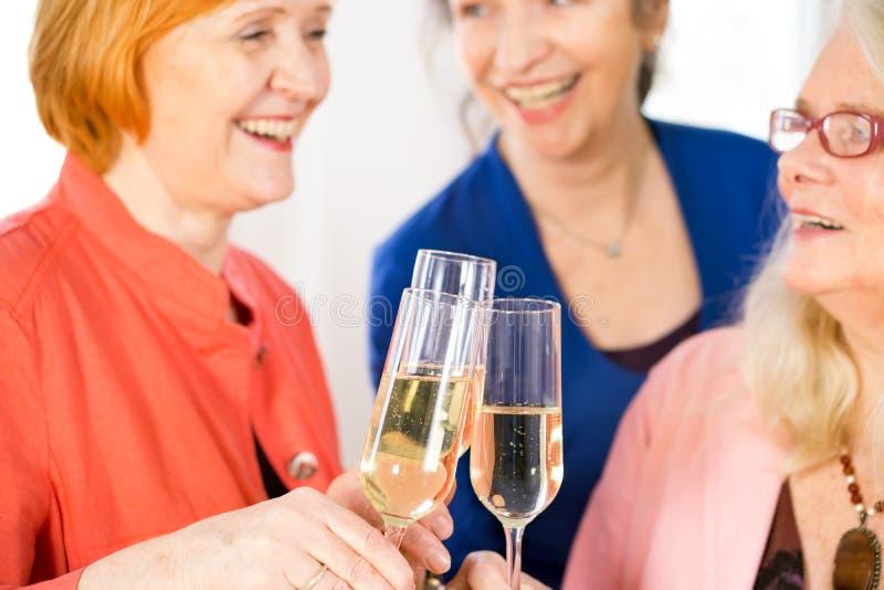 Gläser Weißwein geworfen von den glücklichen erwachsenen Damen stockfotografie