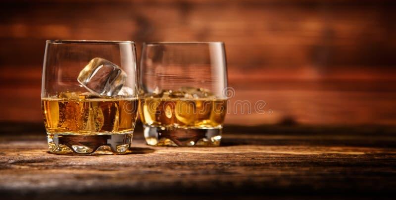 Gläser Whisky mit Eiswürfeln dienten auf Holz stockfoto